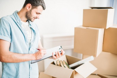 man-with-notebook-among-boxes-housewarming-P24BHR9.jpg